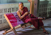 Yangon/Myanmar-01/23/2019: Burmese monk looking at his cell phone on a bench