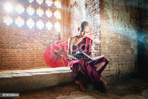 Burmese buddhist Monk in his traditional clothing sitting inside temple reading buddhist book in the light of sunbeams shining through the ornamental temple window. Real People, Natural Interior Temple Light. Bagan, Mandalay Region, Myanmar, Asia.