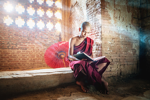 Burmese Novice Buddhist Monk In Temple Reading Bagan Myanmar Stock Photo - Download Image Now