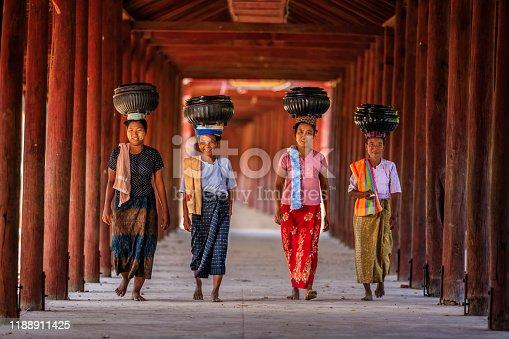 Burmese women carrying bowls of rice to the monastery near Bagan, Myanmar