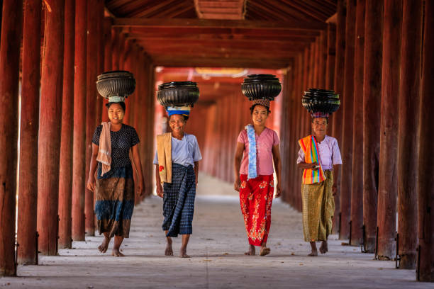 Burmese women carrying bowls of rice to the monastery stock photo