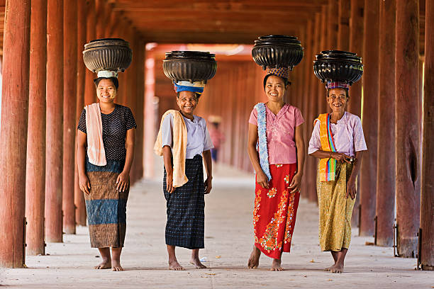 Burmese women carrying bowls of rice to the monastery  myanmar stock pictures, royalty-free photos & images