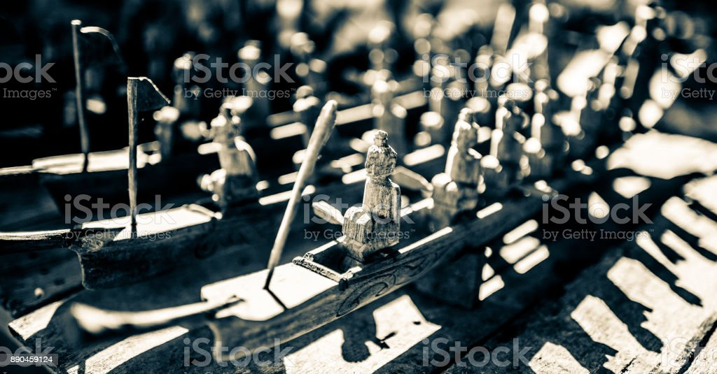 Burmese wood carving of men on longboats stock photo