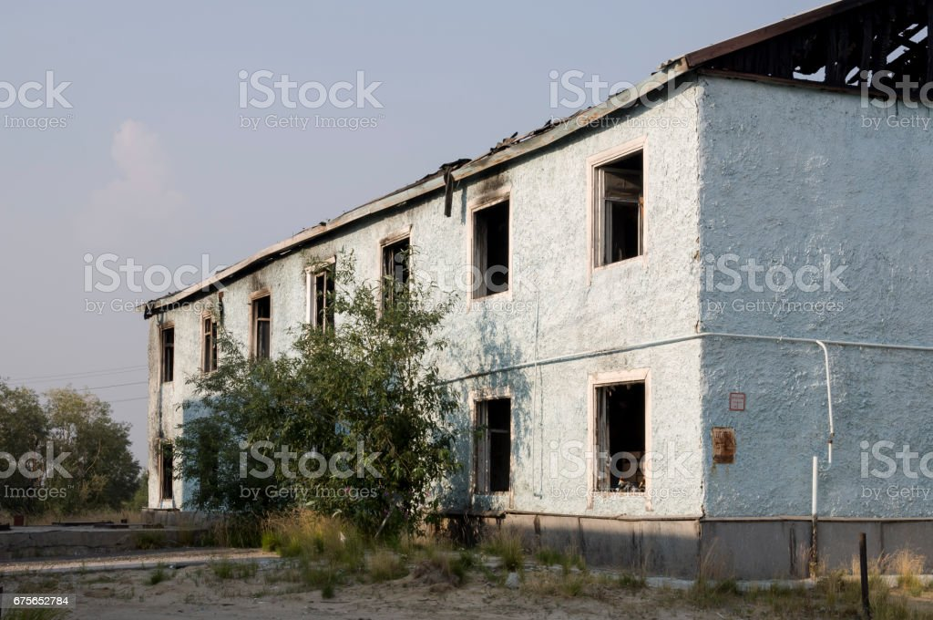 Burnеd light blue two-storeyed building with green trees. After fire royalty-free stock photo