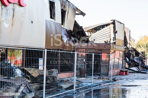 DUCLAIR, FRANCE - OCTOBER Circa, 2018 : Damaged CARREFOUR MARKET supermarket after arson fire with burn debris of twisted metallic structure after intense burning with gate protection
