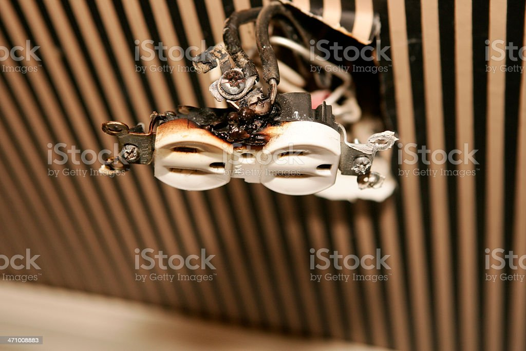 A burned electrical outlet hanging stock photo
