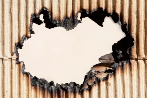 Burned hole in cardboard