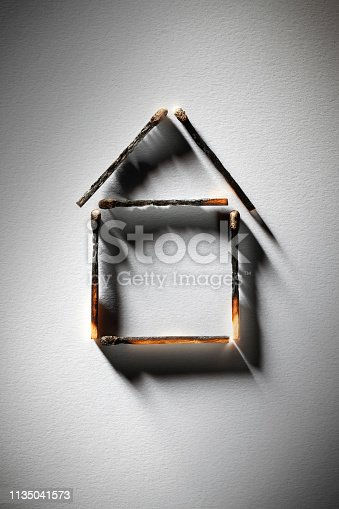 istock Burned house. Burnt matches in the shape of a house. 1135041573