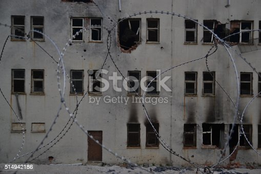 istock Burned House in ruins behind barbed wire. 514942186