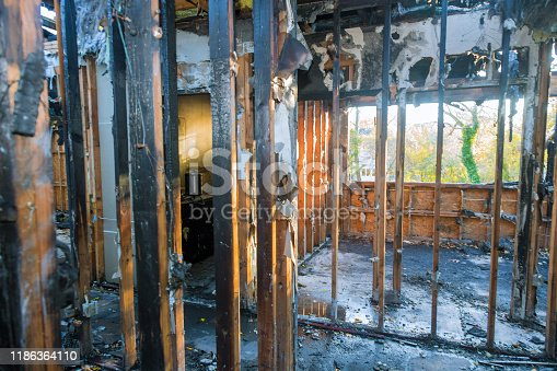 1015604978 istock photo Burned house interior after fire burnt black timber roof structure building room inside 1186364110