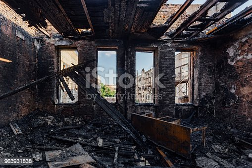 istock Burned interiors after fire in industrial or office building. Burnt furniture 963931838