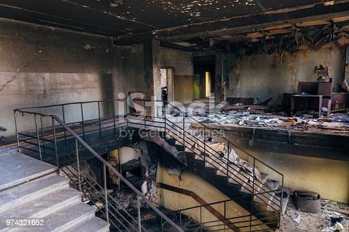 istock Burned interiors after fire in industrial or office building. Walls and staircase in black soot 974321652
