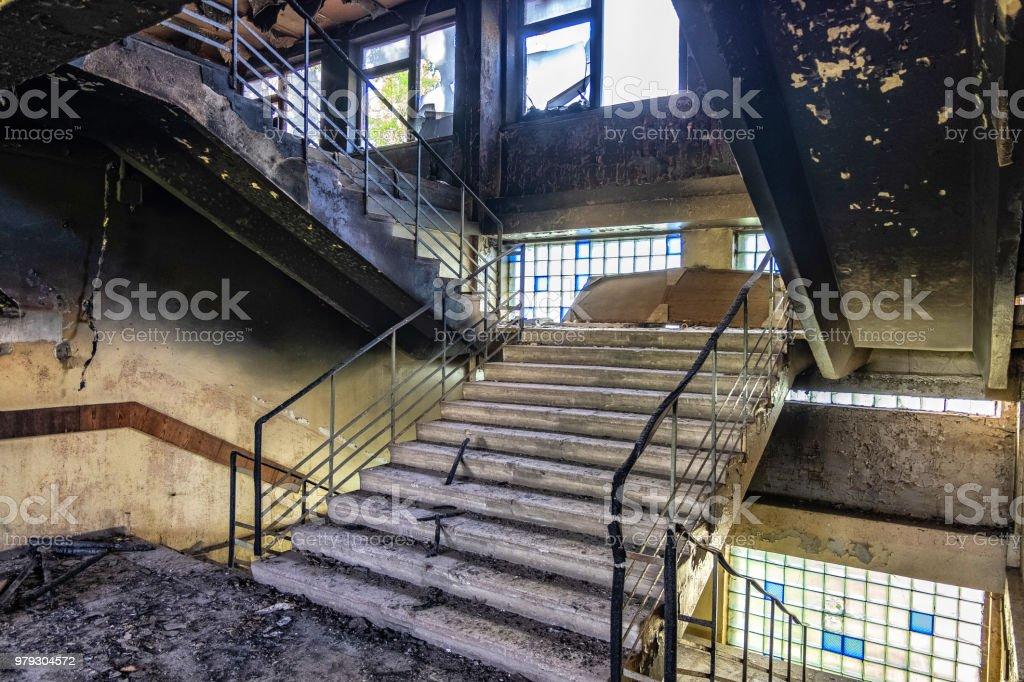 Verbrannte Innenräume nach Brand im Industrie- oder im Büro-Gebäude. Wände und Treppe in Ruß – Foto