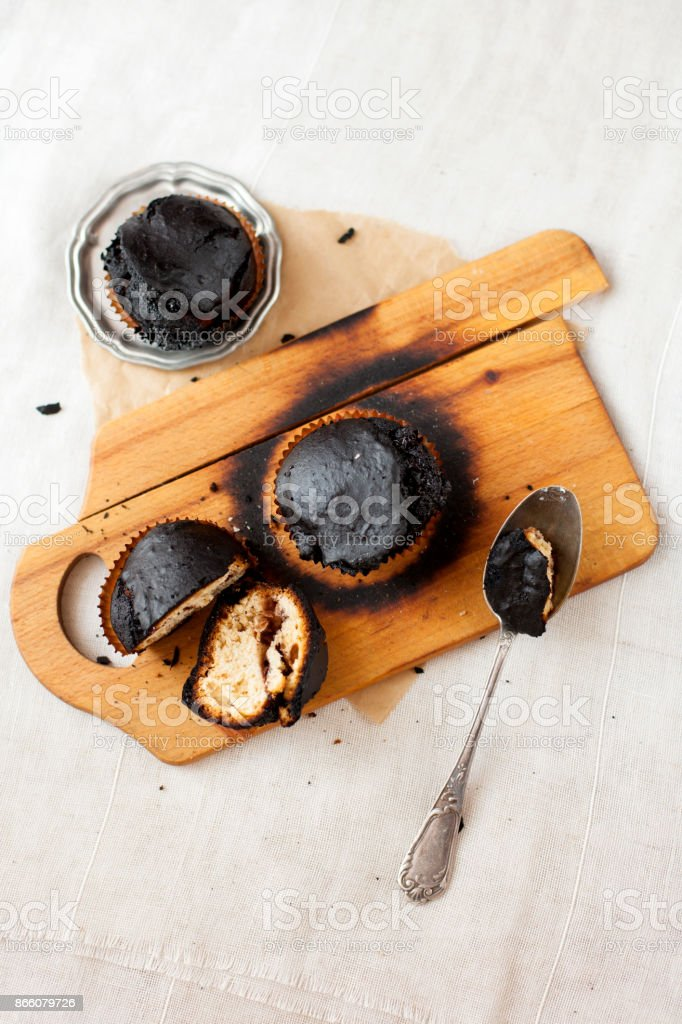 burned muffins - black cupcakes, failed baking, catastrophe in the kitchen, burned on charcoal stock photo