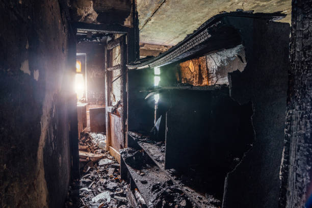 Burned room interior in apartment house. Burned furniture and charred walls in black soot stock photo