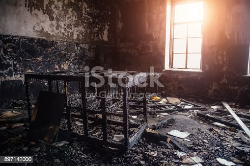 istock Burned room interior in apartment house. Burned furniture and charred walls in black soot 897142000