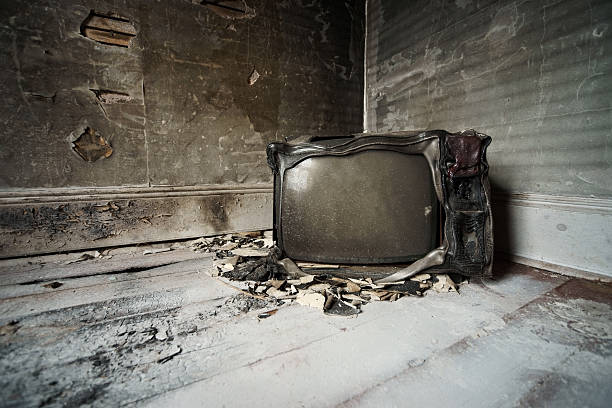 Burned television. A burned television sits in the corner of a fire damaged room in an abandoned house. Light grain has been added to this image. portable television stock pictures, royalty-free photos & images
