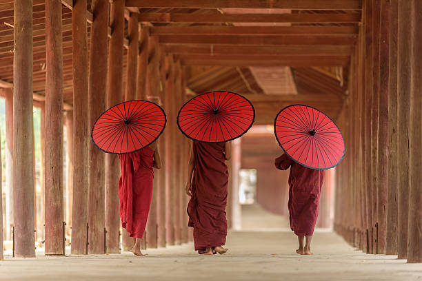 Burnese Buddhist novices Three Buddhist novices with red umbrella on their shoulder are walking inside pagoda in Mandalay Myanmar myanmar stock pictures, royalty-free photos & images