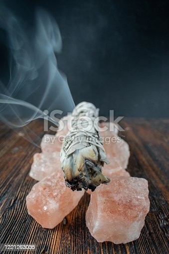 burning a smudge sage stick on a base of pink salt crystals with smoke trail