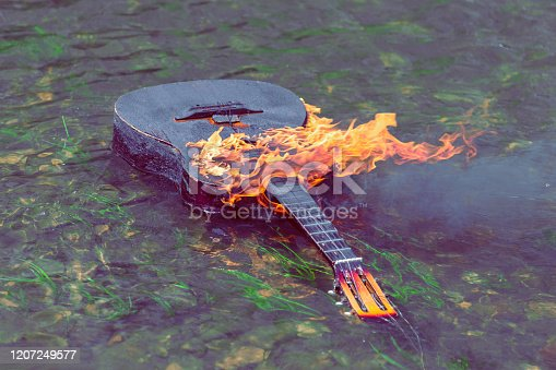 burning acoustic guitar floats on water