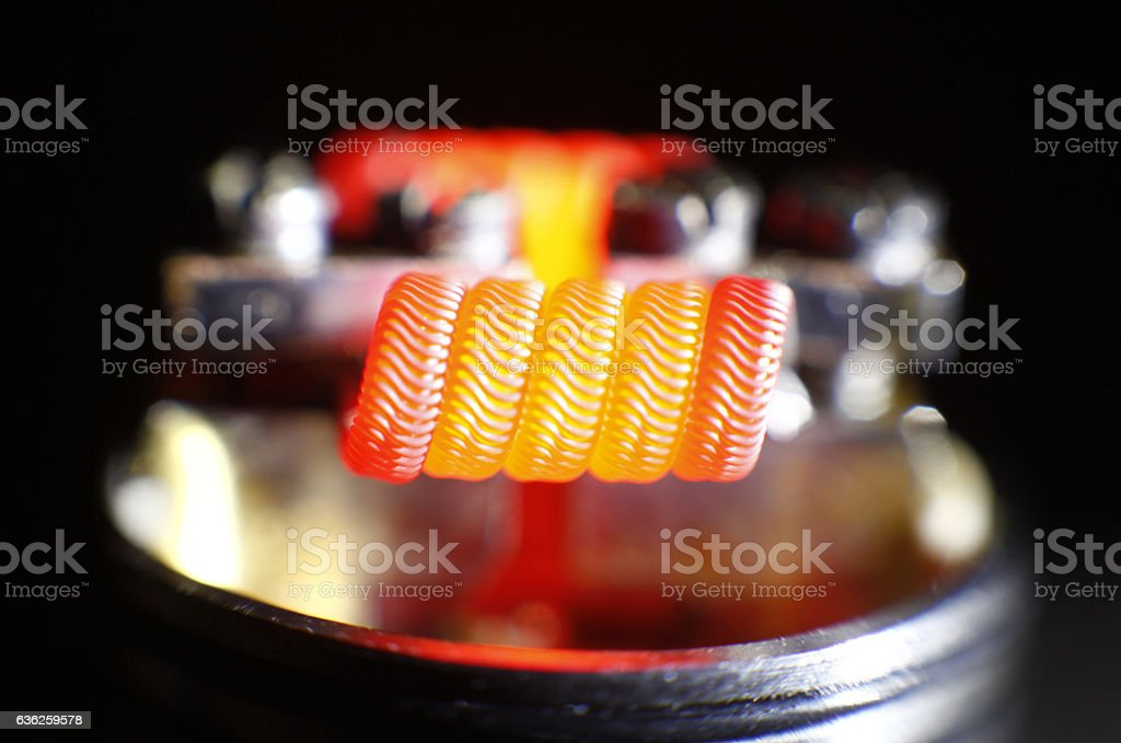Burning alien coil build on vaping rebuildable dripping atomizer stock photo