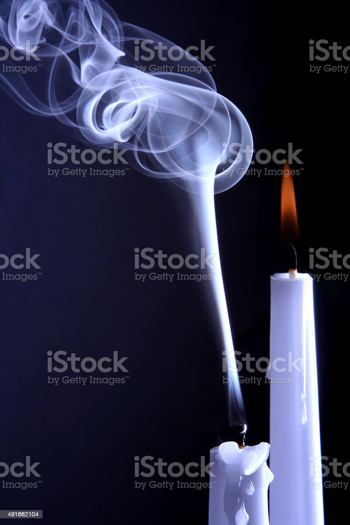 burning and extinguished the candles on dark background stock photo