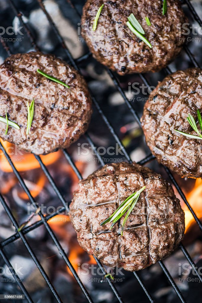 burning beef burgers on bbq flames stock photo