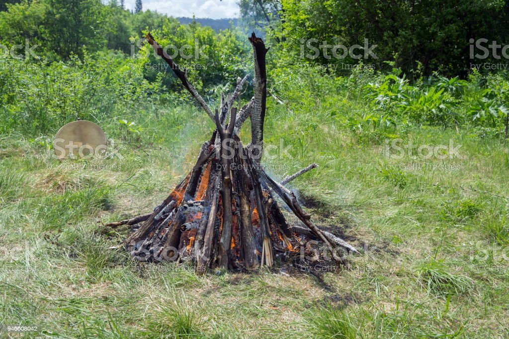 Burning big bonfire and a shamanic tambourine nearby, in the middle of a clearing in a summer forest. stock photo