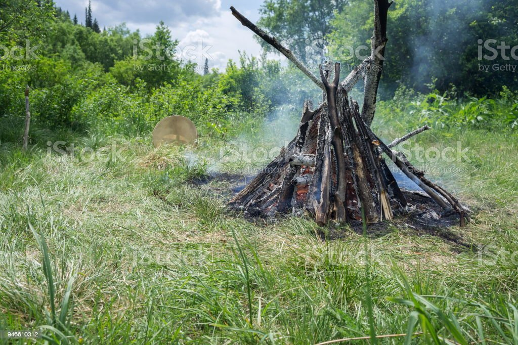A burning big bonfire and a shamanic tambourine nearby, on a green glade in the forest. stock photo