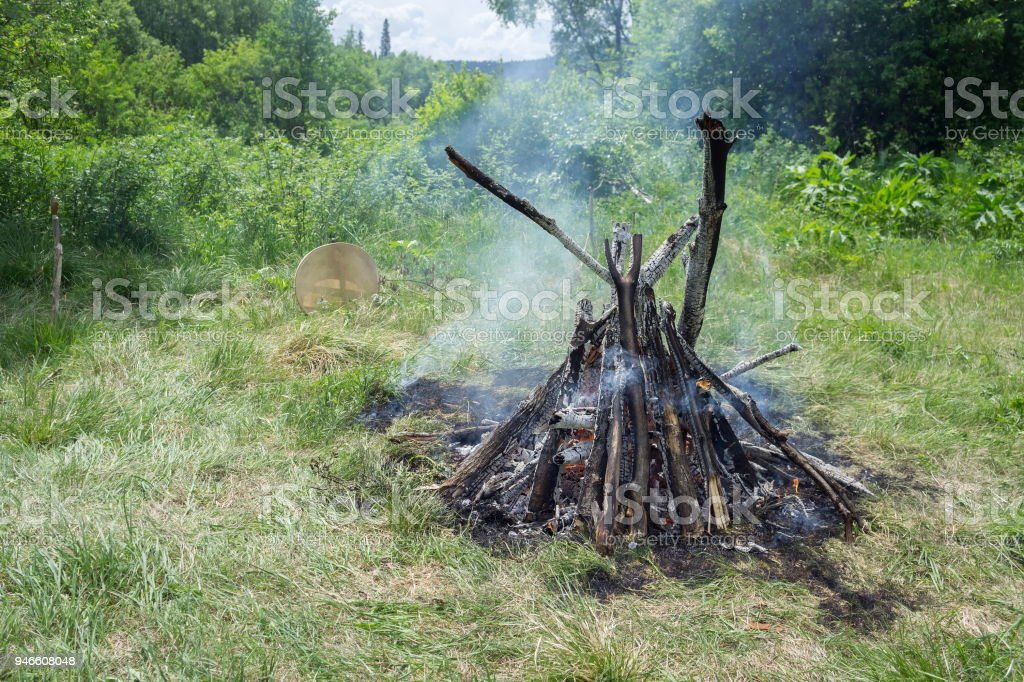 A burning big fire and a shamanic tambourine are nearby in the summer forest. stock photo