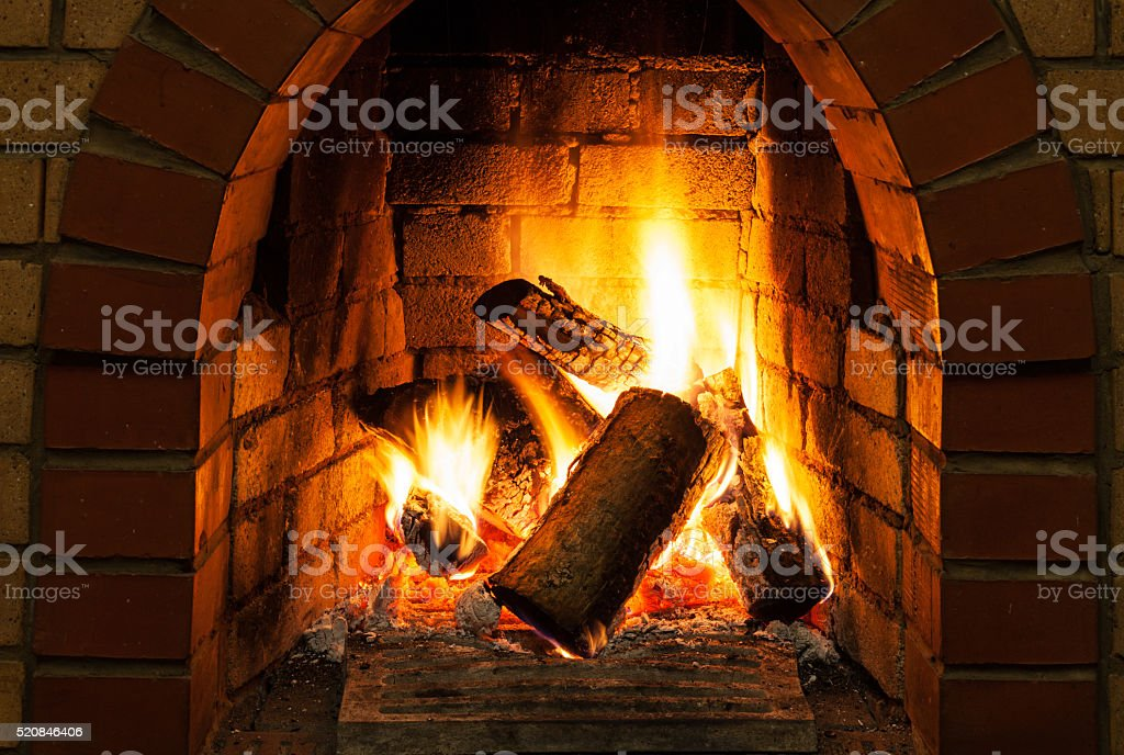burning billets in fire-box of fireplace stock photo