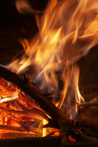 Burning firewood in the fireplace closeup, texture of fire and flame, dark background
