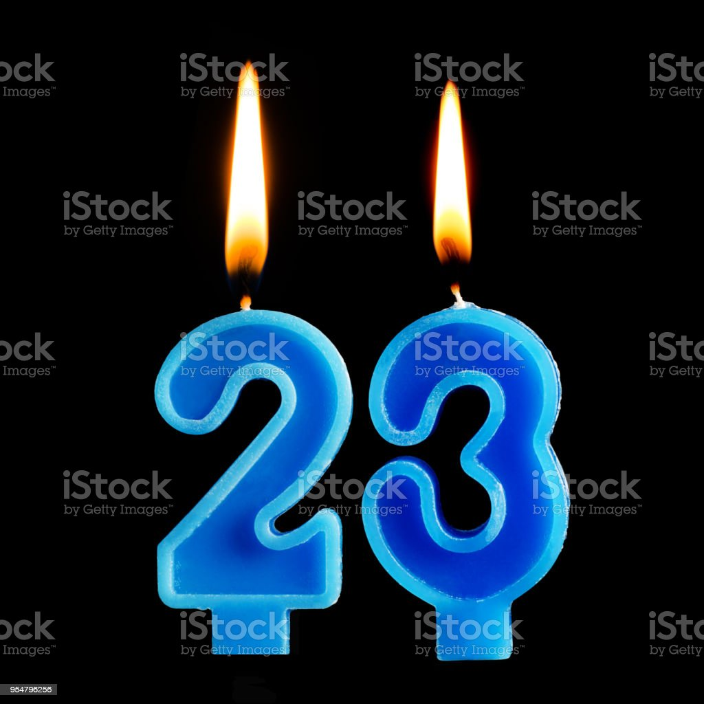 Burning birthday candles in the form of 23 twenty three for cake isolated on black background. The concept of celebrating a birthday, anniversary, important date, holiday stock photo