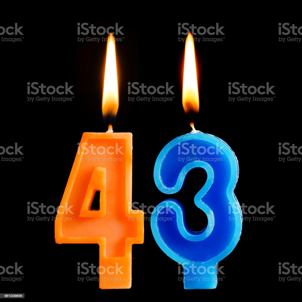 Burning birthday candles in the form of 43 forty three for cake isolated on black background. stock photo