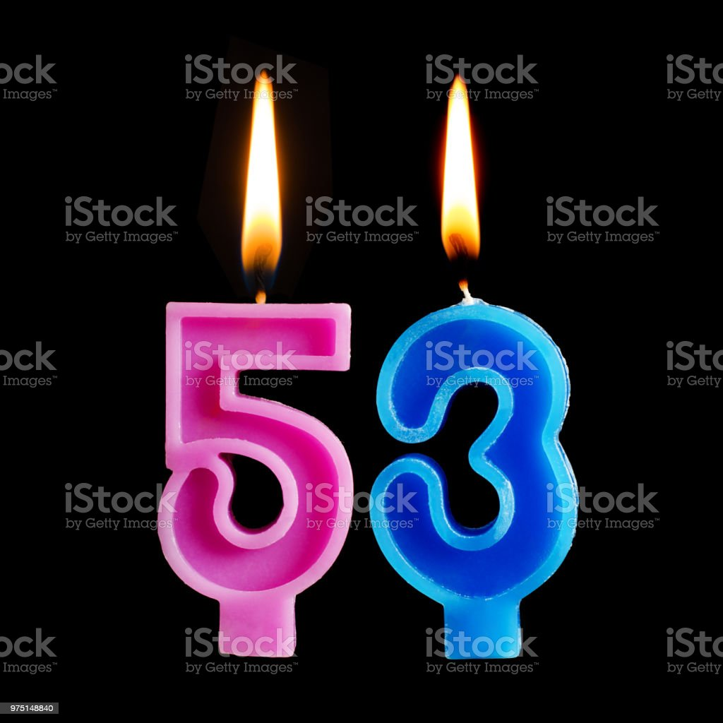 Burning birthday candles in the form of 53 fifty three for cake isolated on black background. stock photo