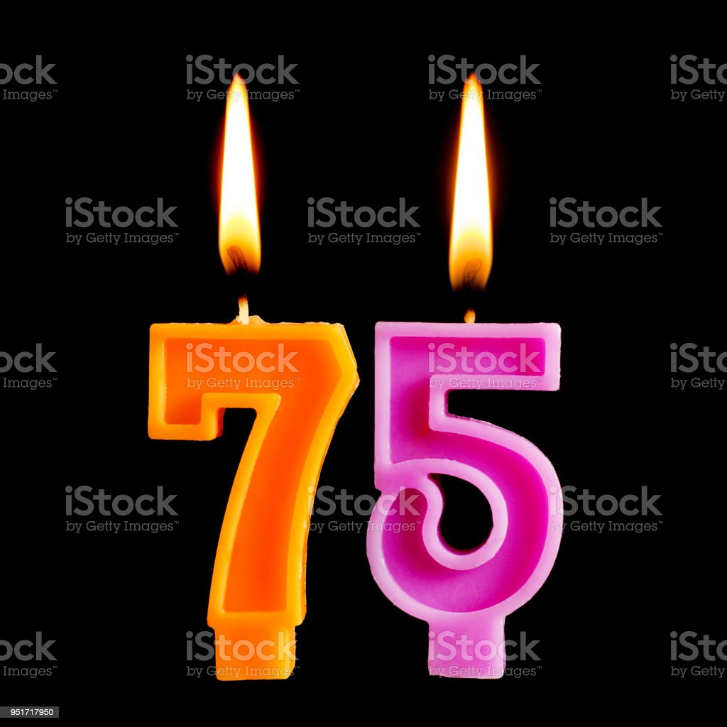 Burning birthday candles in the form of 75 seventy five figures for cake isolated on black background. The concept of celebrating a birthday, anniversary, important date, holiday stock photo