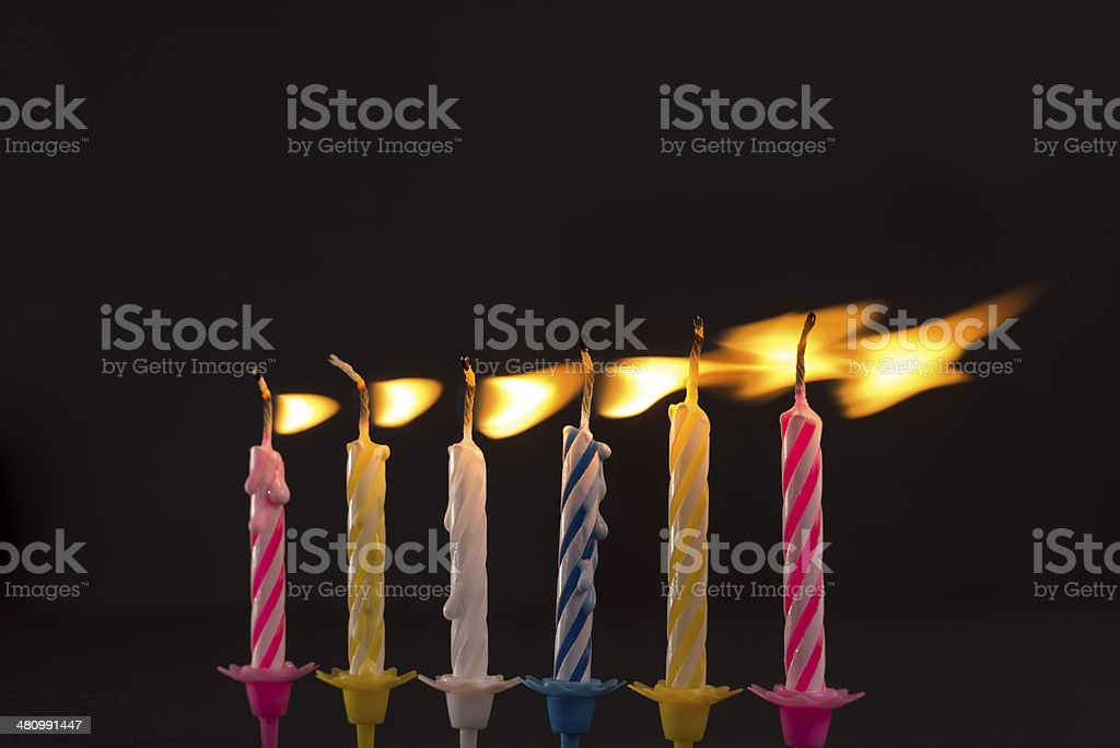 Burning birthday candles in wind stock photo