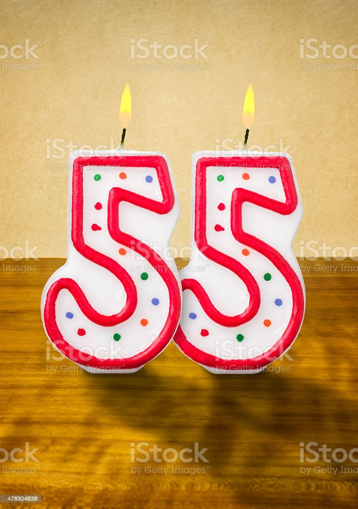 Burning birthday candles number 55 stock photo