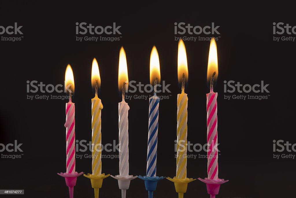 Burning birthday candles on black background stock photo
