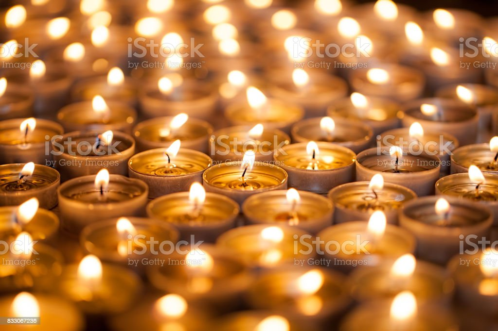 Burning bright. Golden warm glow from candle flames. Many beautiful lit tealight candles glowing. stock photo
