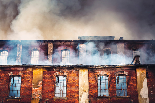 Photo of a burning old red-brick factory with a lot of smoke.