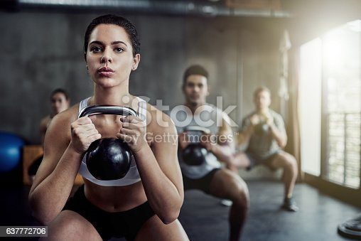 Shot of a fit young woman working out with a kettle bell at the gym