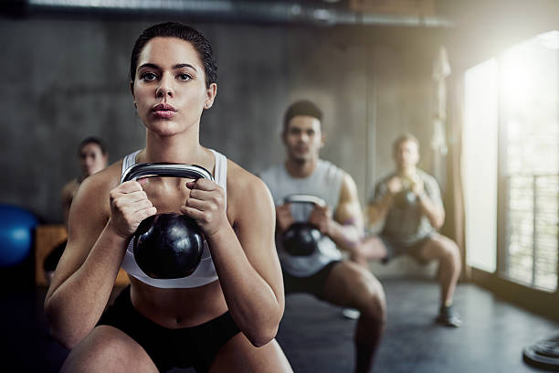 burning calories and strengthening her core with a kettlebell - health club stock photos and pictures