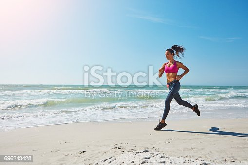 Shot of an attractive young woman working out on the beach