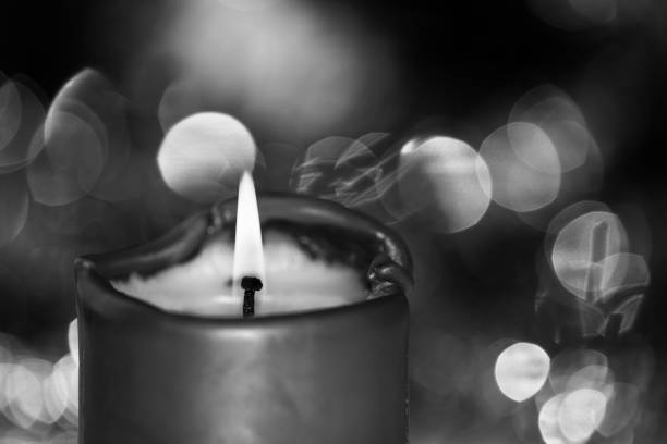 Burning candle against blurred background in black and white stock photo