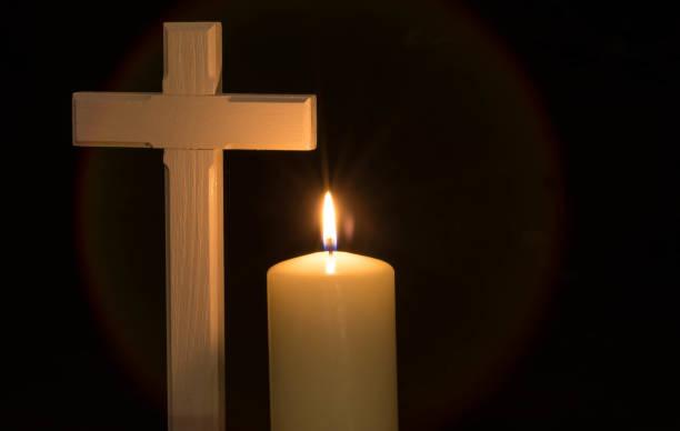 Burning candle and cross on black background stock photo