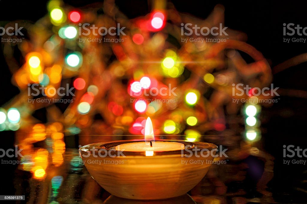 burning candle and many colorful lights stock photo
