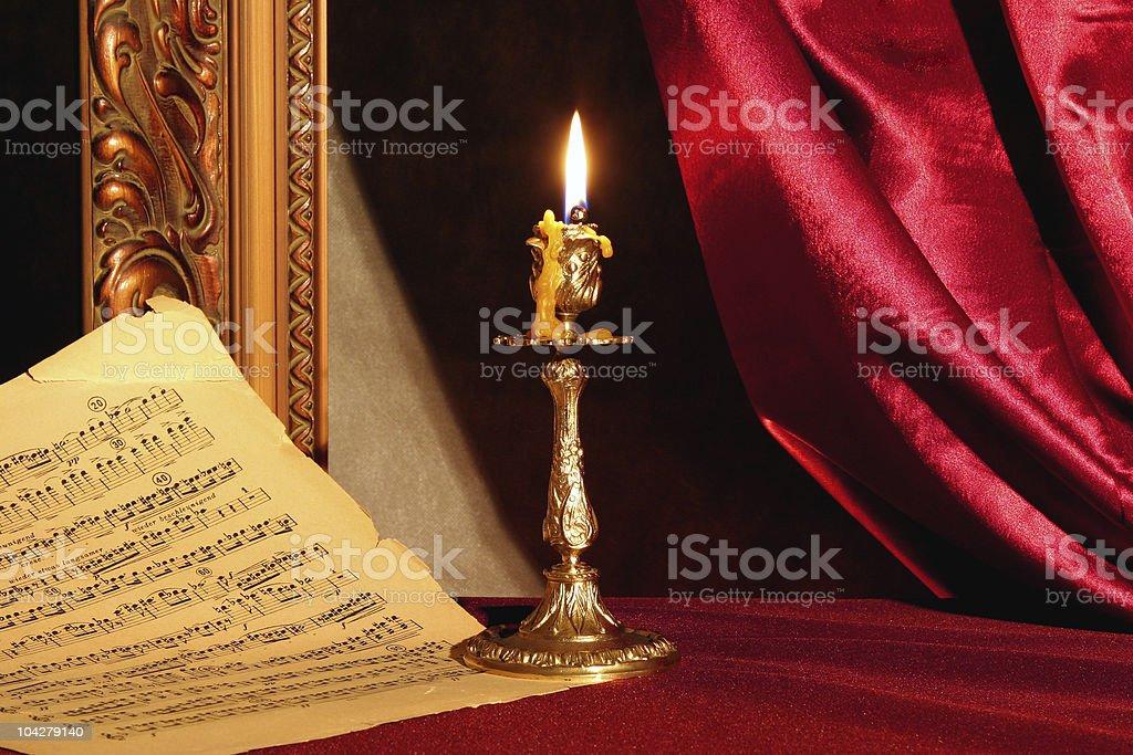 Burning candle and music sheet stock photo