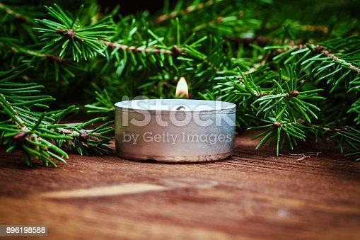 istock A burning candle and spruce branches on a wooden table. Selective focus. Copy space. Christmas, New Year background 896198588