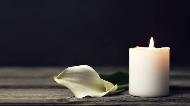 burning candle and white calla on dark background with copy space. sympathy card - funerale foto e immagini stock